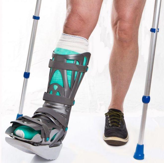 надевать сапог, опираясь на костыль при ходьбе